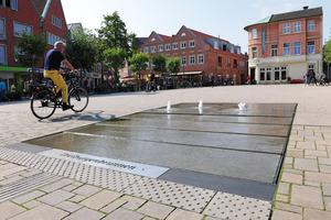 Die großformatigen Natursteinplatten des Brunnenareals sind minimal gestuft, um ein Gefälle zu erzeugen. Dennoch ist die Fläche völlig barrierefrei und kann selbst von Radfahrern durchquert werden.