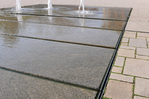 Umlaufende, maßgefertigte Schwerlast-Schlitzrinnen stellen den Wasserkreislauf sicher. Sie greifen passgenau den Gefälleverlauf des Plattenmaterials auf und bilden einen optisch reduzierten Übergang zur Fläche des Marktplatzes.