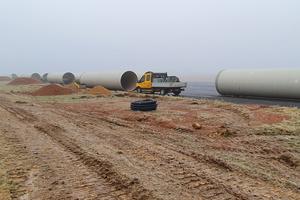 Die GFK-Rohre werden neben dem Rohrgraben auf der Start- und Landebahn gelagert.