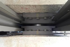 Achtung Spiegelbild! Das Lager (untere Hälfte) spiegelt sich im hochglänzenden Edelstahl-Gleitblech (oben). Oben und unten sind deshalb auch die Klammern gegen abhebende Kräfte doppelt zu sehen.