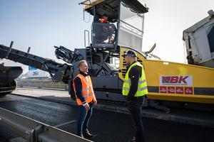 Gut zusammengearbeitet: Alexander Hirsch von der LeFa Finanz Leasing- und Finanzierungsagentur (links) neben Alexander Bermel von BK Asphaltmiet-service (rechts) auf einer Autobahnbaustelle in der Nähe von Krefeld. Im Hintergrund ein Beschicker von BK im Einsatz.