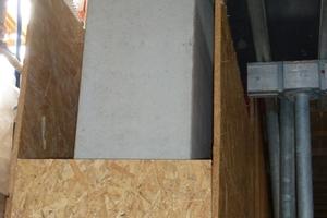 """Unmittelbar nach dem Ausschalen wird die exzellente Betonoberfläche hinter einer Verkleidung aus OSB-Platten """"versteckt"""", damit sie die Bauphase unbeschädigt übersteht."""
