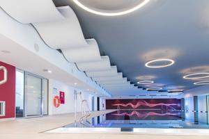 Entspannen unter schwebenden Wellen: elegante Deckengestaltung über dem großzügigen Sport-Pool des body + soul Fitness und Wellness Centers.