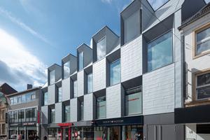 Die Fassadengeometrie folgt dem gebogenen Straßenverlauf.