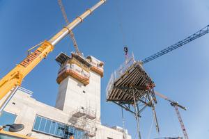 Unter hohen Sicherheitsanforderungen (Windlast, laufender Flugbetrieb) entsteht der neue Vorfeld-Tower mit Hilfe eines kranabhängigen Kletterfahrgerüstes CS 240 L.