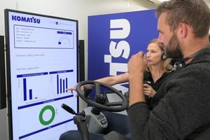 Komatsu stellt bei der Road-Show seine neue Simulatoren für Fahrer-Schulungen vor. Ronja Berg vom Komatsu-Marketing erläutert einem Besucher die Ergebnisse seines Mobilbagger-Einsatzes.
