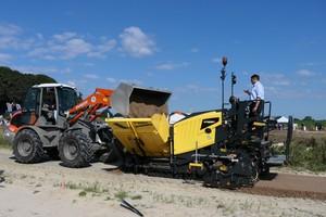 Der Weycor-Radlader AR530 beschickt den Straßenfertiger BF200 von Bomag. Der Hersteller erläutert die Vorteile der Bomap-App, mit der die Arbeitsergebnisse der Erd- und Asphaltverdichtung auf der Baustelle in Echtzeit dokumentiert werden können.