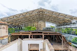 Das LGS 75 Wetterschutzdach auf Basis des Peri Up Gerüstbaukastens ist verfahrbar ausgebildet. So kann einerseits witterungsgeschützt gearbeitet werden, andererseits wird ein Materialtransport mittels Baustellenkran ermöglicht.