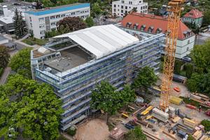 Zur Durchführung der aufwendigen Baumaßnahme muss die Gebäude-substanz des Bestandsbauwerks während der gesamten Umbauphase gegen äußere Witterungseinflüsse geschützt werden.