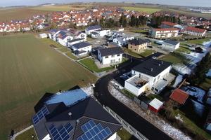 Die Wohnanlage am Ortsrand umfasst sowohl dreigeschossige Mehrfamilienhäuser als auch Ein- und Zweifamilienhäuser – jeweils ausgestattet mit Solarpanelen auf dem Dach.