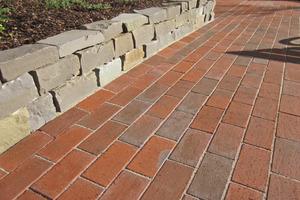 Im Zusammenspiel mit Natursteinmauern setzen die rotbunten Kohlebrandklinker wirkungsvoll Akzente im Garten.<br />