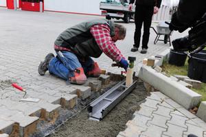 Mitarbeiter der Firma Klaus Brok Garten- und Landschaftsbau brachten die erste Rinne mit Ablaufstutzen an der Verrohrung der Entwässerung an.