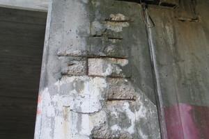 Stützwand im Übergangsbereich zur Spindel. Gut zu sehen ist die geringe Betondeckung der Bewehrung mit großflächigen Abplatzungen.