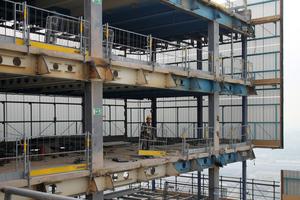 Beim Rückbau des Bayer-Hochhauses klettern bis zu 180 m² große Doka-Schutzschilde Xclimb 60 kranunabhängig Etage für Etage nach unten und sichern den Gebäuderand