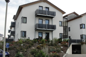Nahansicht der dreigeschossigen Wohnhäuser: Die vier identisch großen Gebäude bergen jeweils sechs Wohneinheiten mit eigenem Balkon oder eigener Terrasse.