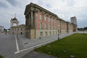 """Große graue Belgrano-Pflastersteine, hier Granitplatten nach historischem Vorbild, wurden in einem regelmäßigen Muster verlegt, was den klassischen Charakter des Stadtschlosses unterstreicht. Der Schriftzug an der Westfassade """"Ceci n'est pas un château."""" (frz. für """"Dies ist kein Schloss."""") ist wohl ein Hinweis darauf, dass die barocke Fassade trügt, denn das Gebäude verbirgt im Inneren ein modern gestaltetes Parlament."""