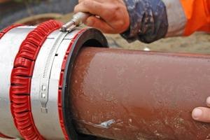 """Mit dem Drehmomentschlüssel wird das Spannband der VPC-Rohrkupplung nach dem Einführen des HS-Kanalrohres angezogen. Auf diese Weise wird das Kunststoffrohr automatisch zentriert<span class=""""4.7 Fotonachweis"""">Fotos: Funke Kunststoffe GmbH</span><br />"""