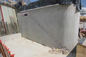 Eine ausgeschalte Kernwand mit abgerundeten Ecken und Brettmuster. An der Wand sieht man den Verlauf der zukünftigen Treppe