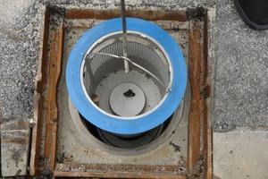 Als letzter Arbeitsschritt wird der Grobfilter eingesetzt, bevor der Straßenablauf mit dem Gussrost verschlossen werden kann