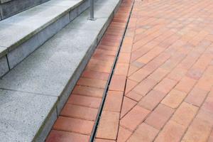 Dränage- und Entwässerungsrinnen der Firma Richard Brink sorgen dafür, dass Niederschlagswasser an den Außenbereichen zuverlässig abgeleitet wird. Die Schlitzrinnen vor den Treppen am Haupteingang dienen der Linienentwässerung.