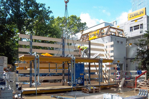 Am TaunusTurm bringt der Kran die durch Doka einsatzfertig vormontierte Selbstkletterschalung SKE 50 plus an ihren Einsatzort
