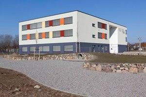 Architektonische Merkmale der neuen Grundschule sind die strenge, rechteckige Kubatur mit ihren waagerecht verlaufenden, bunt gestalteten Fensterbändern sowie das Flachdach mit der umlaufenden Attika