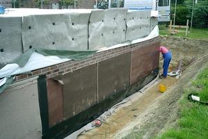 Abdichtung der Wände: zunächst wird die Atmungsfixbahn an der Wand hoch geführt …<br />