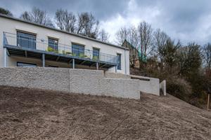Die grob gespitzten Betonmauern sichern das Gelände und nehmen Bezug zu historischen Gemäuern.