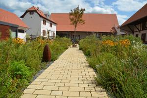 Der natürliche Pflasterbelag Via Natura im Farbton sandgelb texturiert schmückt auch den Kräutergarten des Hofgutes.