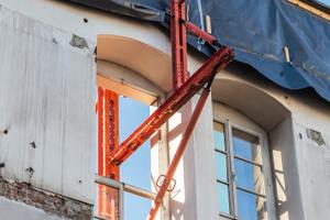 Die exakt an die vorhandenen Fensteröffnungen angepasste Fassadenabstützung basierte auf mietbaren Variokit Systembauteilen.