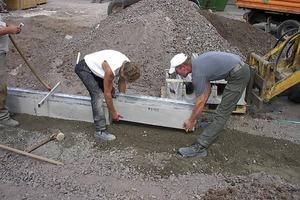 Bild 1 und Bild 2: Vorarbeiten – Erstellung von Fundamenten und Rückenstützen<br />Zunächst ist ein entsprechendes Fundament in der Betongüte entsprechend der späteren Verkehrsbelastung für die Faserfix Super Rinnen zu erstellen. Wenn die Rinne mit ihrer Oberkante am Schnurgerüst entlang führt ist die richtige Einbauposition erreicht. Dann ist je nach Einbauvorschrift eine<br /> Rückenstütze an den Rinnenseiten hochzuziehen und mit dem noch feuchten Fundament zu verbinden. Das nächste Rinnenstück wird mit Hilfe von Falzverbindungen schnell richtig positioniert. Wenn der Rinnenstrang fertig gestellt ist und Fundament und Rückenstütze ausgehärtet sind, wird der angrenzende Oberflächenbelag erstellt. Beim Erstellen von Oberflächen aus Beton sind wirksame Raumfugen in Längs- und Querrichtung gemäß DIN 18318 einzubauen.