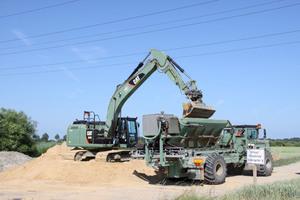 Der Sand wird mit Cat Kettenbaggern 323EL auf Dumper oder Terra Gator verladen