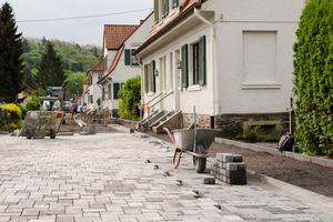 Eine Straße in der Kolonie wird komplett gepflastert. Die Parkbuchten heben sich durch einen etwas dunkleren Farbton ab