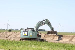 Cat Baumaschinen verrichten entlang der Bautrasse Aushubarbeiten für den fünf Meter breiten Kabelgraben