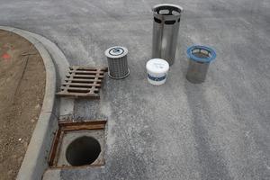 In Bedburg kam das Innolet-Set für quadratische Straßenabläufe der Größe 500 x 500 mm zum Einsatz. Das System besteht aus einem Einsatz (hinten im Bild), einer mit einem speziellen Substrat (weißer Eimer) gefüllten Filterpatrone (li.) und einem Grobfilter (im Bild mit blauem Ring)