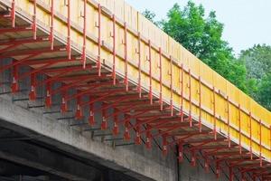 rechts im Bild: Die Konsole wird je nach Kappengeometrie mit horizontalen Fußspindeln (zu sehen vorn im Bild) oder mit diagonalen Spindeln gegen die vorhandene Stahlbetonkonstruktion abgestützt; Brücke Rheintalautobahn bei Dornbirn<br />