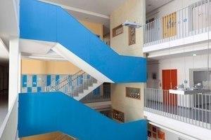 Eyecatcher ist die im kräftigen Blau gestrichene Treppenanlage, über die man aus dem Foyerbereich in alle weiteren Geschosse gelangt