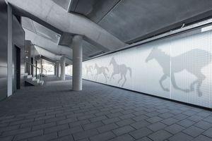 Ein Blick in das Tribüneninnere auf die Glaswand mit den Pferde-motiven. Die Pflasterung mit MultiTec-Aqua wird hier fortgeführt.