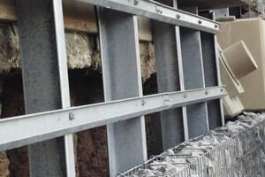 """Im Luftbereich der Stützwand sichern zusätzlich Dauerlitzenanker die Standfestigkeit. Diese """"Felsnägel"""" reichen bis zu 30 m in den Untergrund. Jeder von ihnen kann eine Zugkraft von 1 600 kN aufnehmen, was einer Gewichtskraft von 160 t entspricht"""