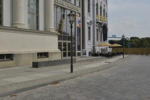 Am angrenzenden Filmmuseum umrahmen rund 500 Tonnen geschnittene Blöcke, Bodenplatten und Blockstufen aus dem Granitstein Leuco-Gabbro die großen Pflanzflächen auf dem Vorplatz.